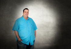 Happy fat man. With blue shirt on a over gray background Stock Photos