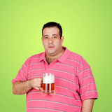Happy fat man drinking a beer. And a green background Royalty Free Stock Image