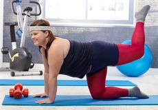 Happy fat woman doing gymnastics royalty free stock photography