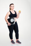 Happy fat woman holding weighing machine and apple Royalty Free Stock Image
