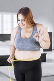 Happy fat woman measures her tummy Stock Images