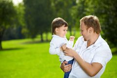 Happy father. Father holds on hands small son in a summer garden royalty free stock image