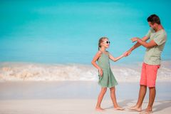 Happy father and his adorable little daughter at tropical beach having fun. Happy father and adorable little daughter at tropical beach having fun Royalty Free Stock Photos