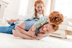 Happy father with adorable redhead children playing and having fun together on floor. Family fun at home concept Royalty Free Stock Photo