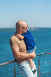 Happy father with baby boy stand on jetty by the river. Royalty Free Stock Images