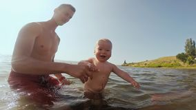 Happy father and baby having fun in the sea, exercising in water.  stock footage