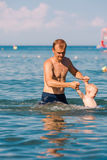 Happy father and baby having fun in the sea Royalty Free Stock Photos
