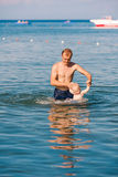 Happy father and baby having fun in the sea Stock Photography