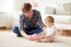 Happy father with baby and piggy bank at home Royalty Free Stock Photography