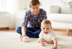 Happy father with baby and piggy bank at home Stock Images