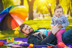 Happy father and baby playing in the park Stock Photos