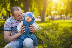 Happy father and baby are playing in the park Stock Photos