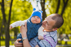 Happy father and baby are playing in the park Stock Images