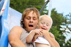 Happy Father and Baby Sliding. An attractive young father and his baby boy are smiling as they go down a slide at the playground on a summer day stock photo