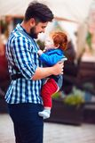 Happy father with baby in sling backpack having a walk in the city stock photography