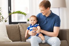 Happy father with baby son sitting on sofa at home stock photography