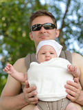 Happy father carries his baby in the carrier. Royalty Free Stock Photos