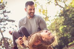 Happy father carrying daughter in arms, laughing and have fun. stock photo