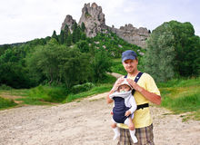 Happy father is carrying his baby in the knapsack. Happy father is carrying his baby in the comfortable knapsack. Dad is holding cute little baby boy. Man and ( Royalty Free Stock Images