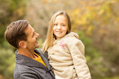 Happy father carrying his cute daughter on an autumns day Stock Images