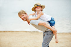 Happy father carrying his daughter on his back Stock Photos
