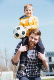 Happy father carrying his little son on shoulders Royalty Free Stock Images