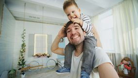 Happy father carrying his smiling son on neck and making selfie on smartphone in bedroom Stock Photos