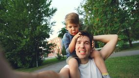 Happy father carrying his smiling son on neck and making video selfie at smartphone camera during walk in park. POV of happy father carrying his smiling son on stock footage