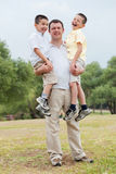 Happy father carrying his two son in his hands Royalty Free Stock Photography