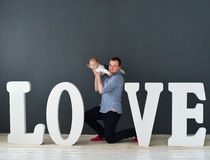 Happy father carrying son isolated on gray background near large letters of the word love Royalty Free Stock Images