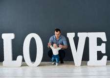 Happy father carrying son isolated on gray background near large letters of the word love. Happy father carrying son isolated on grey background near large Stock Photography