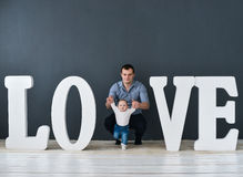 Happy father carrying son isolated on gray background near large letters of the word love. Happy father carrying son isolated on grey background near large Stock Image