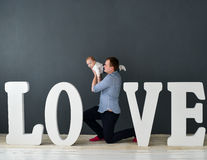 Happy father carrying son isolated on gray background near large letters of the word love. Happy father carrying son isolated on grey background near large Royalty Free Stock Image