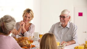 Happy father carving turkey at head of table Royalty Free Stock Images