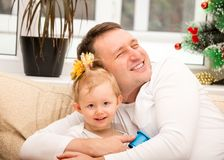 Happy father and child girl hugging and laughing at home. Royalty Free Stock Image