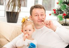 Happy father and child girl hugging and picking his nose on  white background.  Royalty Free Stock Photography