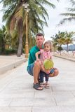 Happy father with a child hug and smile, they are holding a coconut. royalty free stock photo