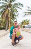 Happy father with a child hug and smile, they are holding a coconut. stock images