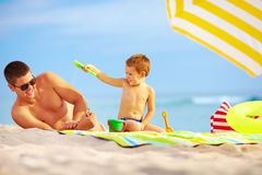 Happy father and child playing on the beach. Happy father and child having fun in sand on the beach royalty free stock image