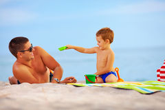 Happy father and child playing on the beach Stock Photos