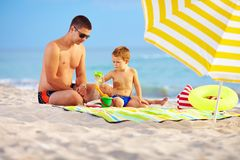 Happy father and child playing on the beach Stock Photo