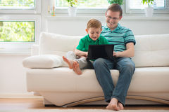 Happy father and child playing at home stock photo