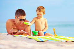 Happy father and child playing in sand on the beach Royalty Free Stock Photo