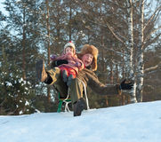 Happy father with child sliding on sleds Royalty Free Stock Photo