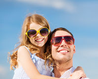 Happy father and child in sunglasses over blue sky Royalty Free Stock Photo