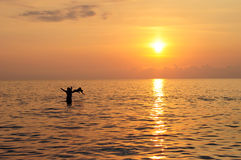 Happy father and child swimming in the sea at beautiful colorful sunset royalty free stock images