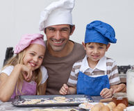 Happy father and children baking cookies together Royalty Free Stock Photo