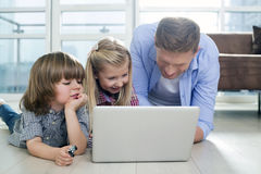 Happy father with children using laptop on floor in living room Royalty Free Stock Photography