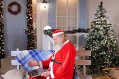 Funny Santa Claus showing thumbs up and working with laptop. Royalty Free Stock Images