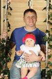 Happy father with cute baby sits on swing. Overgrown with green ivy Stock Image